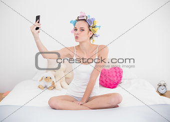 Amused natural brown haired woman in hair curlers taking a picture of herself with mobile phone
