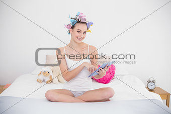 Amused natural brown haired woman in hair curlers using a tablet pc