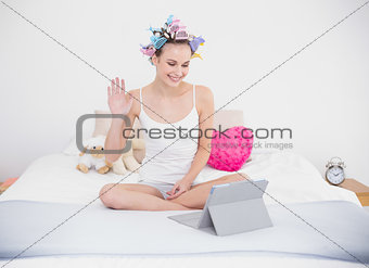Charming natural brown haired woman in hair curlers chatting online with a tablet pc