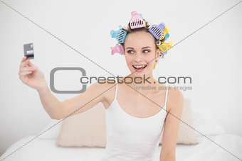 Excited natural brown haired woman in hair curlers holding a credit card