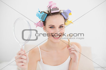 Charming natural brown haired woman in hair curlers holding a mirror and an eyelash curler