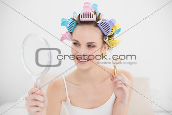Beautiful natural brown haired woman in hair curlers looking herself in a mirror