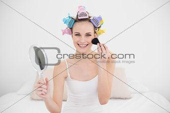 Joyful natural brown haired woman in hair curlers applying powder on her face