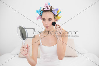 Pouting natural brown haired woman in hair curlers applying powder on her face