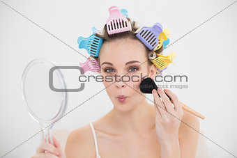 Funny natural brown haired woman in hair curlers applying powder on her face