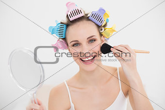 Smiling natural brown haired woman in hair curlers applying powder on her face