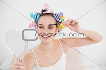 Attractive natural brown haired woman in hair curlers applying mascara