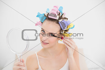 Beautiful natural brown haired woman in hair curlers applying mascara