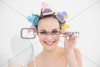 Charming natural brown haired woman in hair curlers plucking her eyebrows