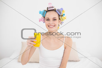 Charming natural brown haired woman in hair curlers holding a glass of orange juice