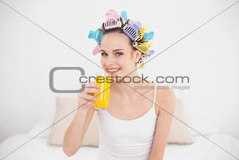 Cute natural brown haired woman in hair curlers drinking orange juice