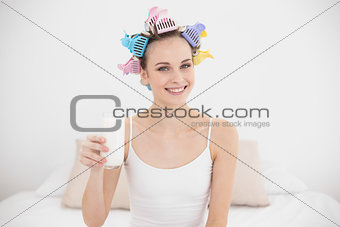 Casual natural brown haired woman in hair curlers holding a glass of milk