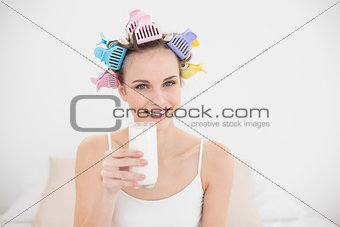Beautiful natural brown haired woman in hair curlers holding a glass of milk