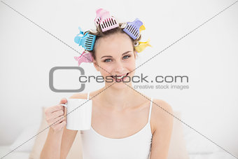 Amused natural brown haired woman in hair curlers holding a mug of coffee