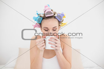 Peaceful natural brown haired woman in hair curlers enjoying coffee smell