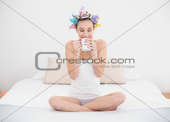 Calm natural brown haired woman in hair curlers enjoying coffee smell