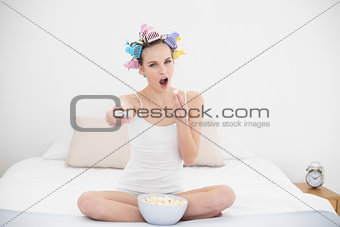 Amused natural brown haired woman in hair curlers watching tv while eating popcorn