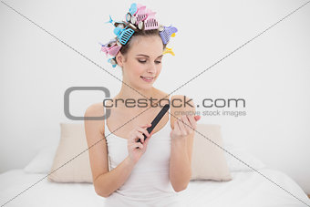 Focused natural brown haired woman in hair curlers filing her nails