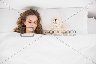 Beautiful brunette sleeping next to teddy bear