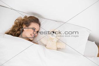 Smiling brunette lying next to teddy bear