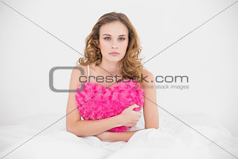 Content attractive brunette holding heart pillow