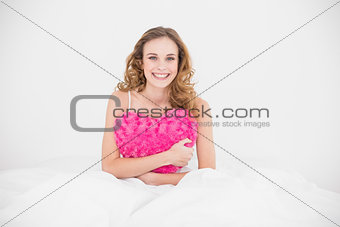 Smiling attractive brunette holding heart pillow