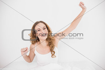 Smiling attractive brunette stretching out one arm