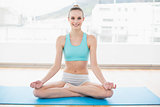 Sporty smiling woman sitting cross-legged on exercise mat