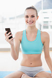 Sporty smiling woman holding phone while sitting on exercising mat