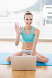 Sporty smiling woman sitting cross-legged in front of laptop waving