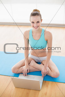 Sporty cheerful woman sitting cross-legged in front of laptop