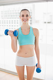 Sporty smiling woman holding dumbbells