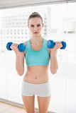 Sporty serious woman holding dumbbells