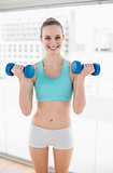 Sporty cheerful woman holding dumbbells