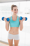 Sporty cheerful woman holding dumbbells and looking away
