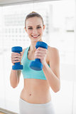 Sporty happy woman holding dumbbells