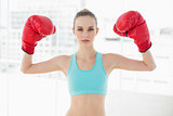 Sporty stern woman holding up boxing gloves