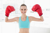Sporty smiling woman holding up boxing gloves
