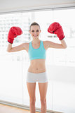 Sporty cheerful woman holding up boxing gloves