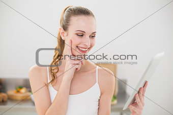 Cheerful young woman holding her tablet pc