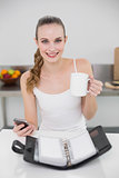 Smiling young woman holding a mug and smartphone with open diary