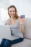 Laughing young woman sitting on couch using laptop for online shopping