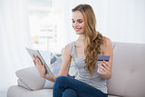 Smiling young woman sitting on couch using tablet for shopping online