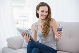Pretty young woman sitting on couch using tablet for shopping online