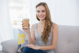 Pretty young woman sitting on couch holding disposable cup