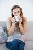 Young woman sitting on sofa drinking from mug