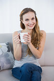 Happy young woman sitting on sofa holding mug