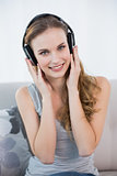 Happy young woman sitting on sofa listening to music