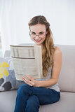 Smiling young woman sitting on sofa reading newspaper