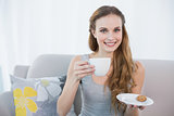 Cheerful young woman sitting on sofa holding cup and saucer